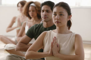 Woman in row of people meditating in yoga class